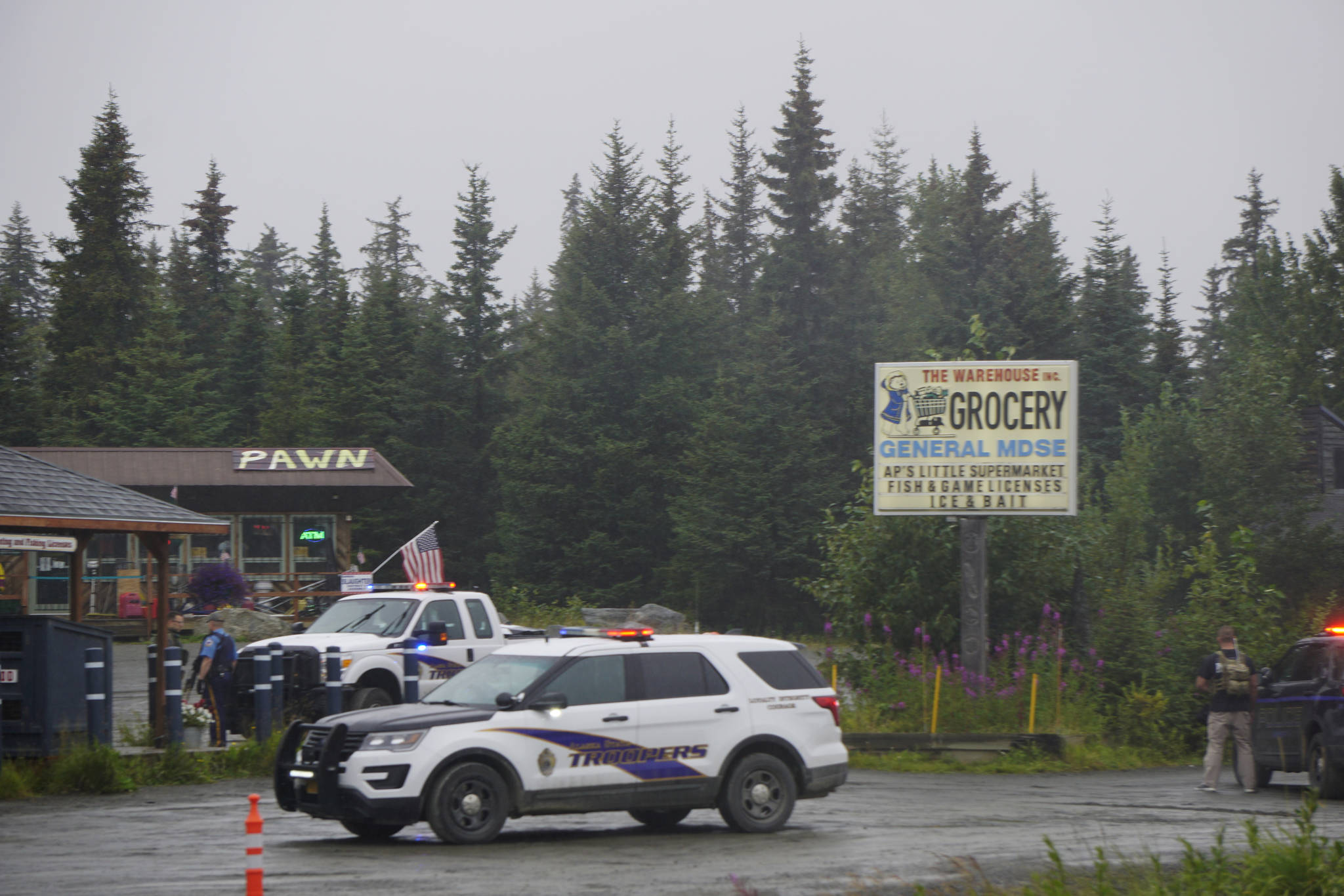 Alaska State Troopers investigate a shooting scene on Monday, Aug. 23, 2021, at the Anchor Point Warehouse in Anchor Point, Alaska at the store on the Sterling Highway in which an Alaska State Trooper was shot. Troopers were searching for the alleged shooter, Bret Herrick, 60. (Photo by Michael Armstrong/Homer News)