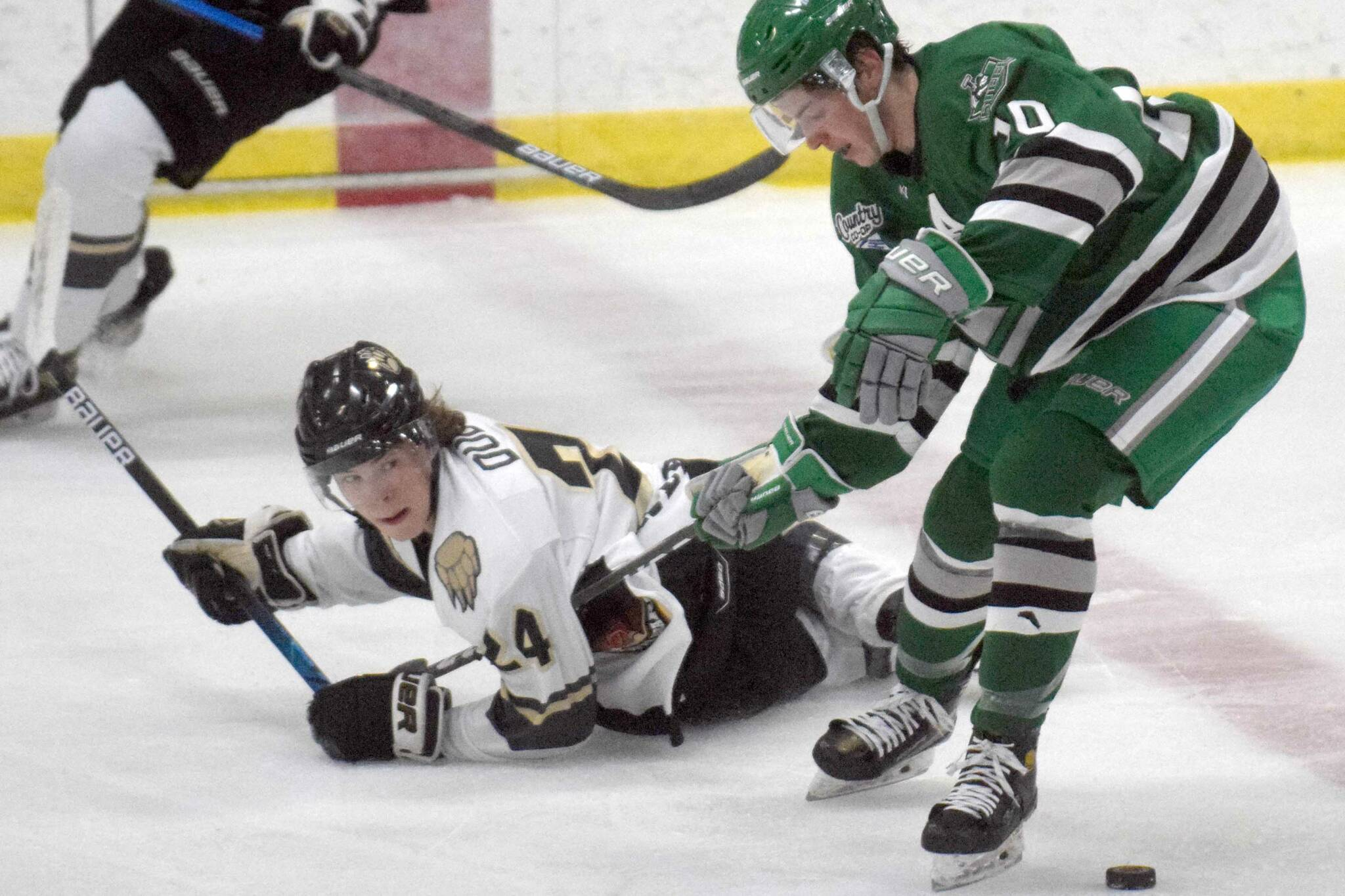 Brown Bears forward Cole Dubicki and Chippewa (Wisconsin) Steel forward Ethan Benz tangle for the puck Thursday, Oct. 21, 2021, at the Soldotna Regional Sports Complex. (Photo by Jeff Helminiak/Peninsula Clarion)